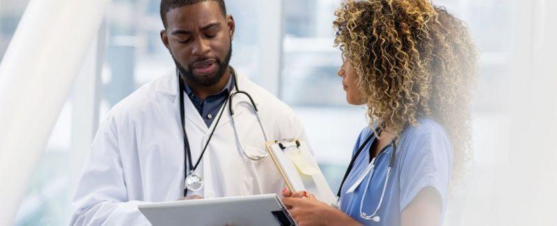 Doctor And EKG Technicians Review EKG Tape